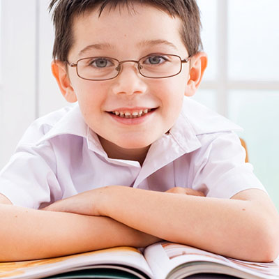 Smiling boy wearing glasses reading a book.