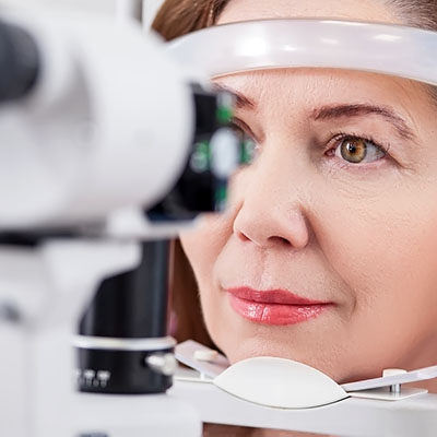 A woman having her eyes examined with a slitlamp during an eye test.